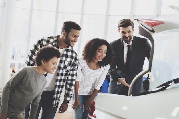 Familie, die autokofferraum-leute-kauf-fahrzeug untersucht. Premium Fotos