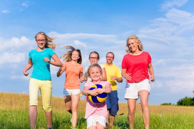 Familie, die ballspiele auf wiese spielt Premium Fotos