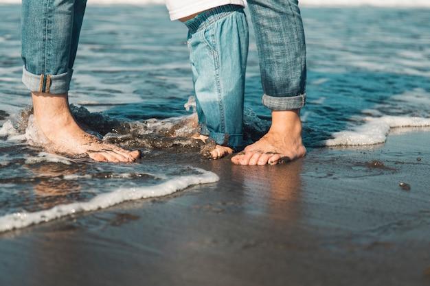 Familie, die barfuß auf nassem sand am strand steht Kostenlose Fotos