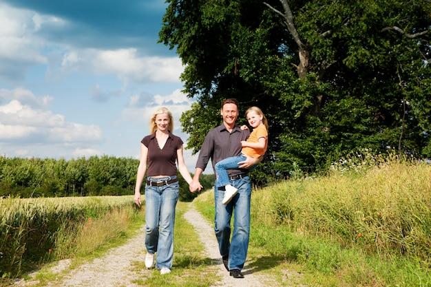 Familie, die ein tragendes kind des wegs hat Premium Fotos