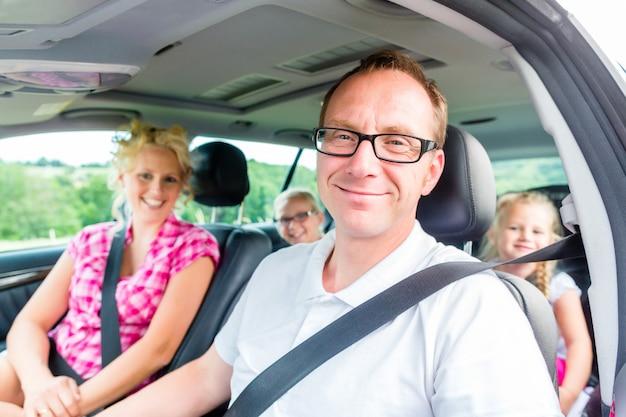 Familie, die in auto mit dem sicherheitsgurt befestigt fährt Premium Fotos