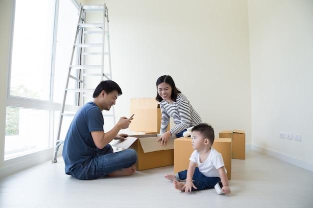Familie, die kästen im neuen haus an beweglichem tag auspackt Premium Fotos