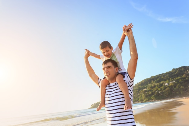 Familie, die mit dem sohn auf dem strand zur sonnenuntergangzeit spielt Premium Fotos