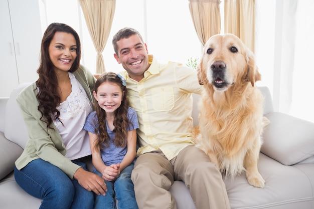 Familie, die mit hund auf sofa sitzt Premium Fotos