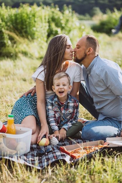 Familie, die picknick isst und pizza im park isst Kostenlose Fotos