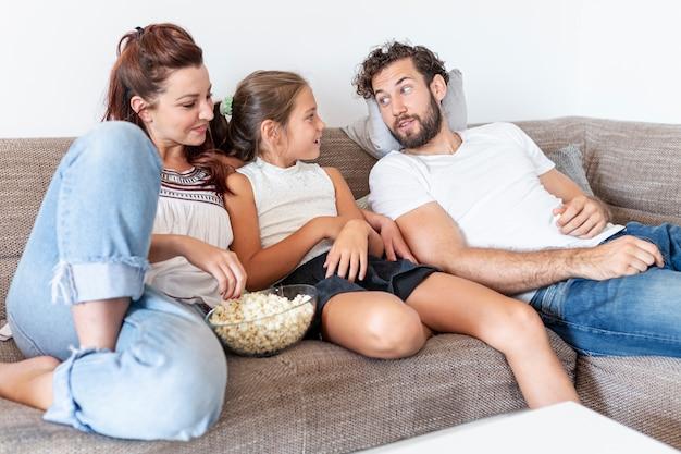 Familie, die popcorn auf der couch isst Kostenlose Fotos