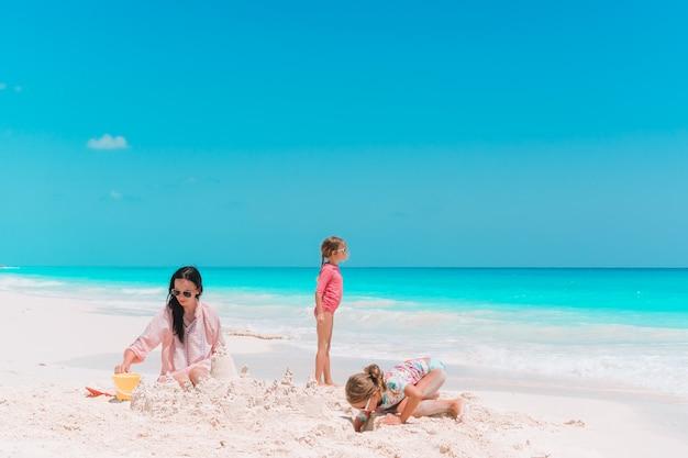Familie, die sandburg am tropischen weißen strand macht. bemuttern sie und zwei mädchen, die mit sand auf tropischem strand spielen Premium Fotos
