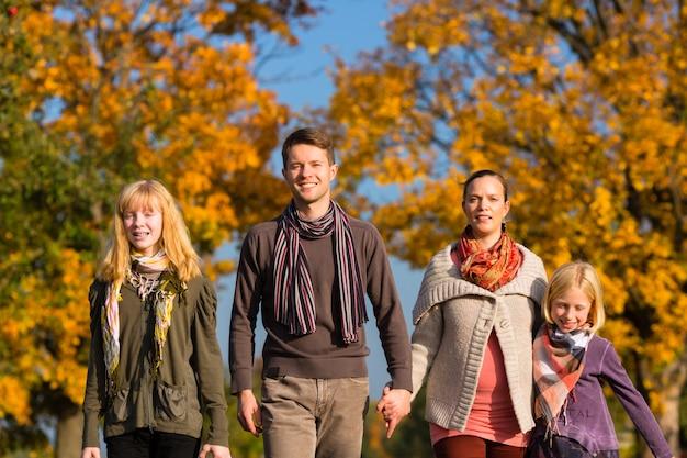 Familie, die weg vor bunten bäumen im herbst hat Premium Fotos