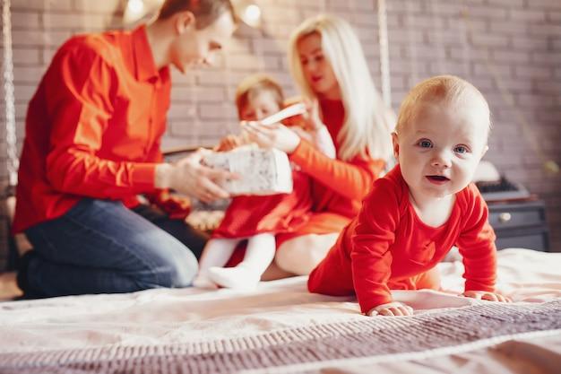 Familie, die zu hause auf einem bett sitzt Kostenlose Fotos