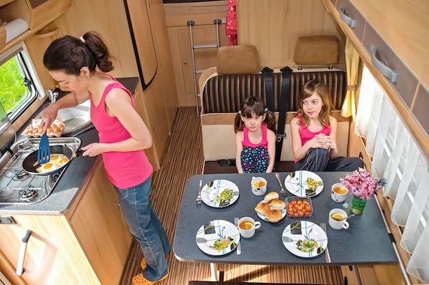 Familie, die zusammen im wohnmobilinnenraum isst, reisen mutter und kinder im wohnmobil im familienurlaub mit kindern Premium Fotos