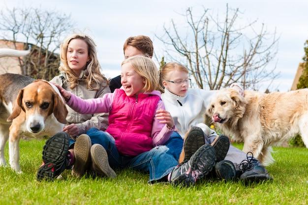 Familie, die zusammen mit hunden auf einer wiese sitzt Premium Fotos