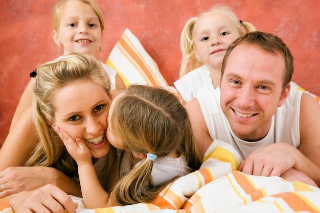 Familie im bett, ein kleiner kuss Premium Fotos