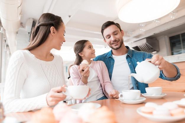 Familie im café-vati gießt tee-kind hat kleinen kuchen. Premium Fotos