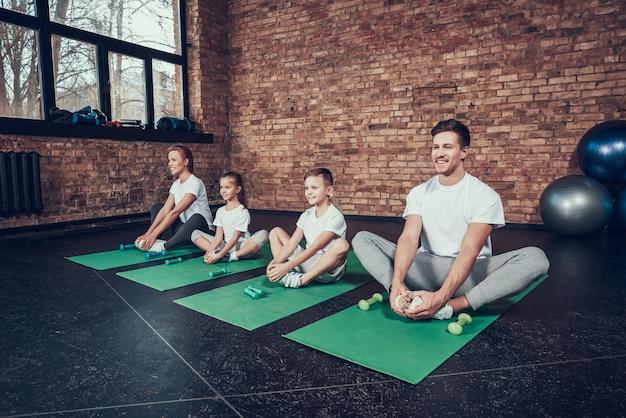 Familie im sport praktizieren yoga und halten daumen hoch Premium Fotos