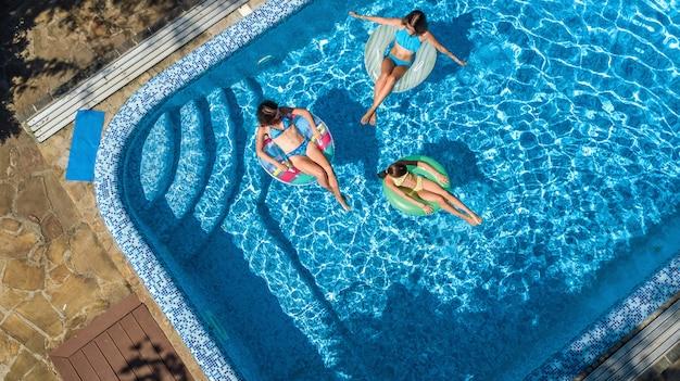 Familie im swimmingpool von der luftbrummenansicht Premium Fotos