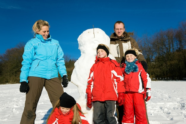 Familie im winter vor ihrem schneemann stehen Premium Fotos