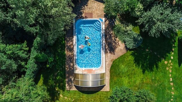 Familie in der swimmingpoolluftbrummenansicht von oben, glückliche mutter und kinder schwimmen auf aufblasbaren ringschaumgummiringen und haben spaß im wasser auf familienferien, tropische feiertage auf erholungsort Premium Fotos