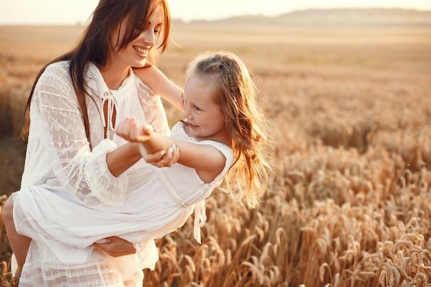 Familie in einem sommerfeld. sinnliches foto. süßes kleines mädchen. frau in einem weißen kleid. Kostenlose Fotos