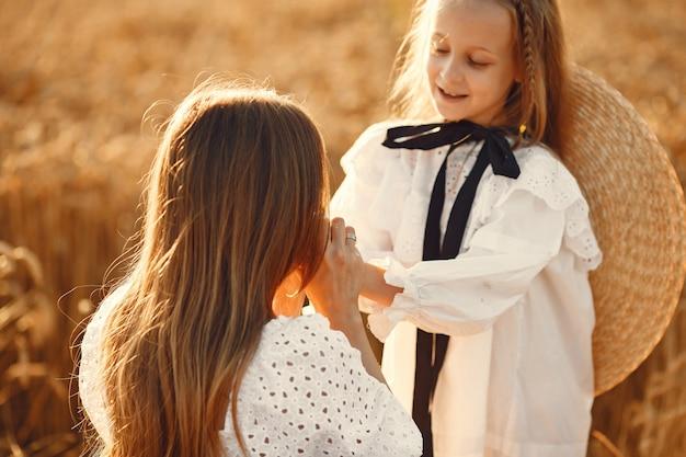 Familie in einem weizenfeld. frau in einem weißen kleid. mädchen mit strohhut. Kostenlose Fotos