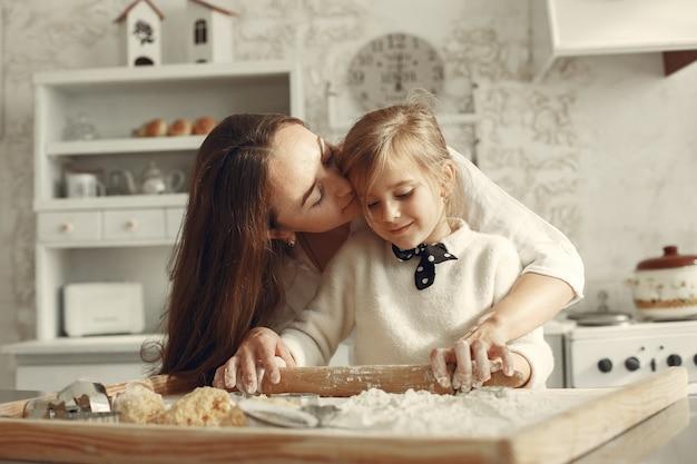 Familie in einer küche. schöne mutter mit kleiner tochter. Kostenlose Fotos