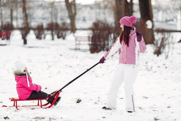 Familie in gestrickten wintermützen auf familienweihnachtsferien. frau und kleines mädchen in einem park. leute, die mit schlitten spielen. Kostenlose Fotos