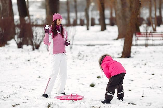 Familie in gestrickten wintermützen auf familienweihnachtsferien. frau und kleines mädchen in einem park. leute spielen. Kostenlose Fotos