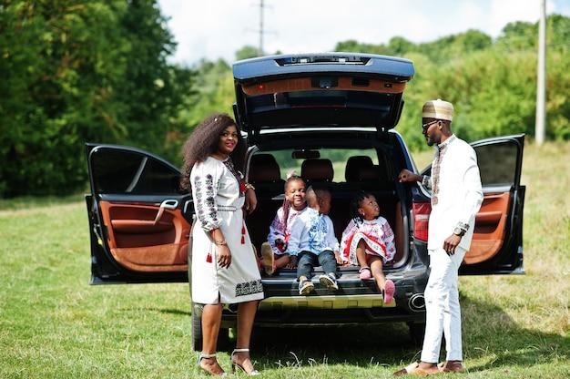 Familie in traditioneller kleidung steht gegen ihr auto, kinder sitzen auf kofferraum Premium Fotos