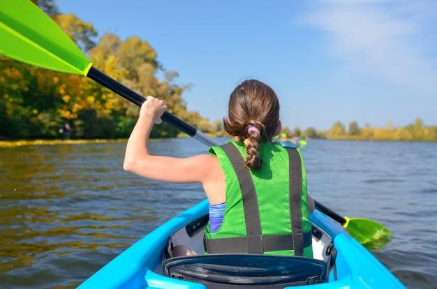 Familie kajak, kind paddeln im kajak auf fluss kanu tour, kind am aktiven herbstwochenende und urlaub Premium Fotos