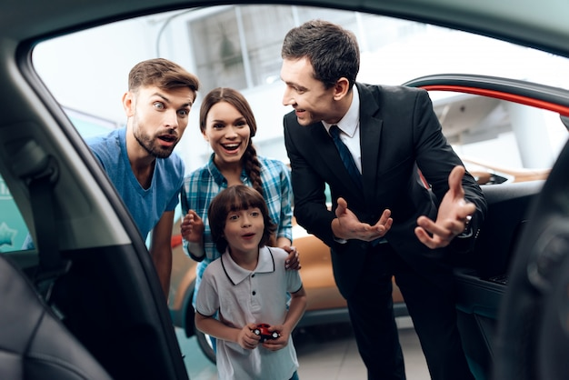 Familie kam zum autosalon, um ein neues auto zu wählen. Premium Fotos