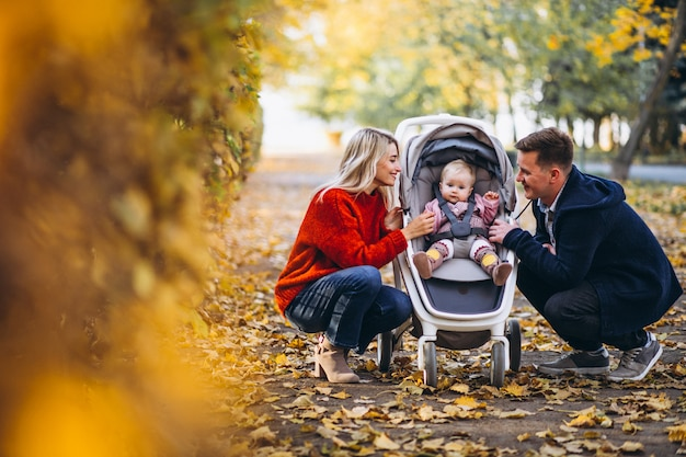 Familie mit dem baby daugher, das in einen herbstpark geht Kostenlose Fotos