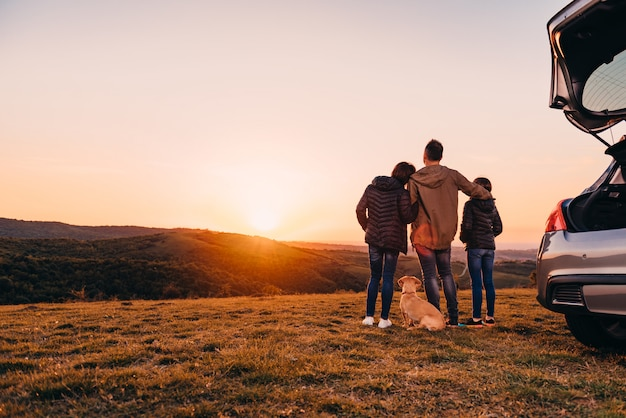 Familie mit dem hund, der am hügel umfasst und sonnenuntergang betrachtet Premium Fotos