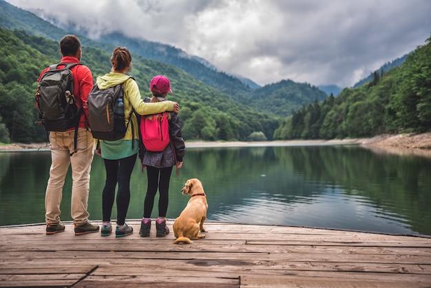 Familie mit dem hund, der auf einem pier steht Premium Fotos