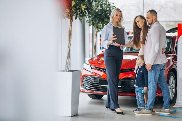 Familie mit dem sohn, der ein auto in einem autosalon wählt Kostenlose Fotos