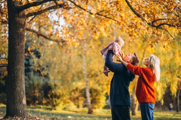 Familie mit der babytochter, die in einen herbstpark geht Kostenlose Fotos