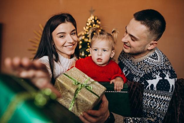 Familie mit der kleinen tochter, die durch weihnachtsbaum sitzt und geschenkbox auspackt Kostenlose Fotos
