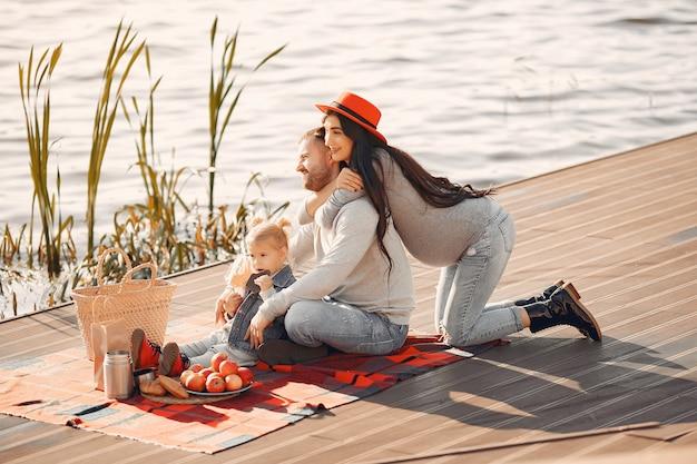 Familie mit der kleinen tochter, die nahe wasser in einem herbstpark sitzt Kostenlose Fotos