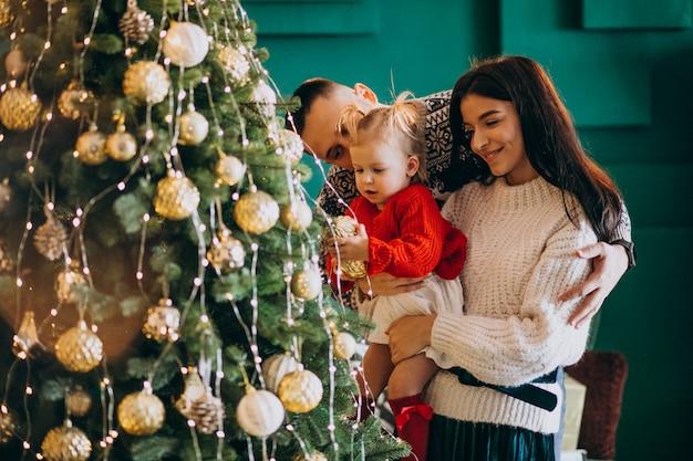 Familie mit hängenden spielwaren der kleinen tochter am weihnachtsbaum Kostenlose Fotos
