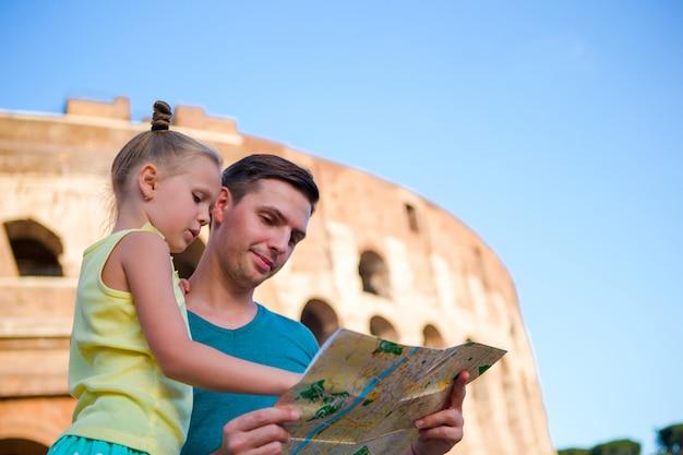 Familie mit karte vor dem kolosseum. vater und mädchen, die den anziehungskrafthintergrund der berühmte bereich in rom, italien suchen Premium Fotos