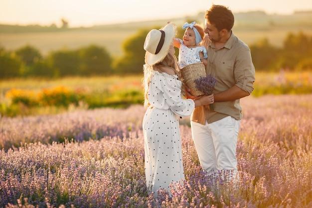 Familie mit kleiner tochter auf lavendelfeld. schöne frau und niedliches baby, das im wiesenfeld spielt. familienurlaub im sommertag. Kostenlose Fotos