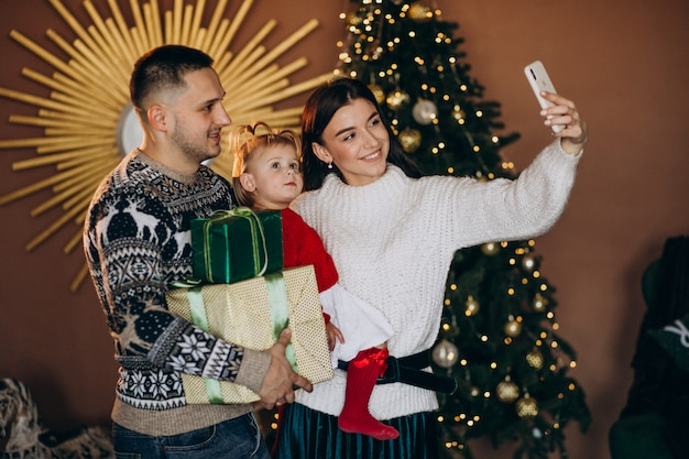 Familie mit kleiner tochter durch den weihnachtsbaum, der geschenkbox auspackt Kostenlose Fotos