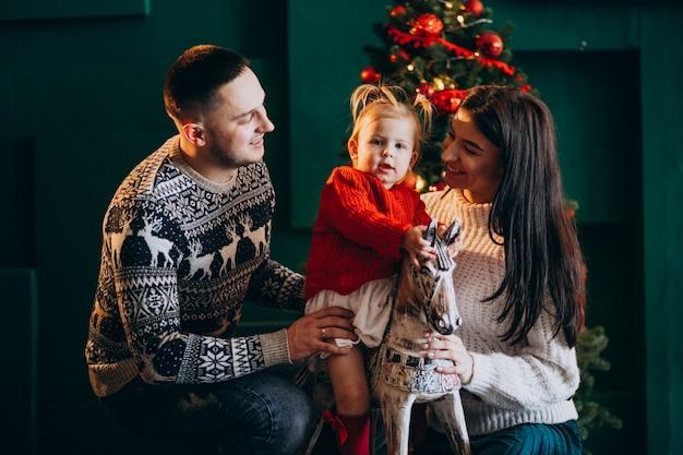 Familie mit kleiner tochter durch den weihnachtsbaum, der mit hölzernem pony spielt Kostenlose Fotos