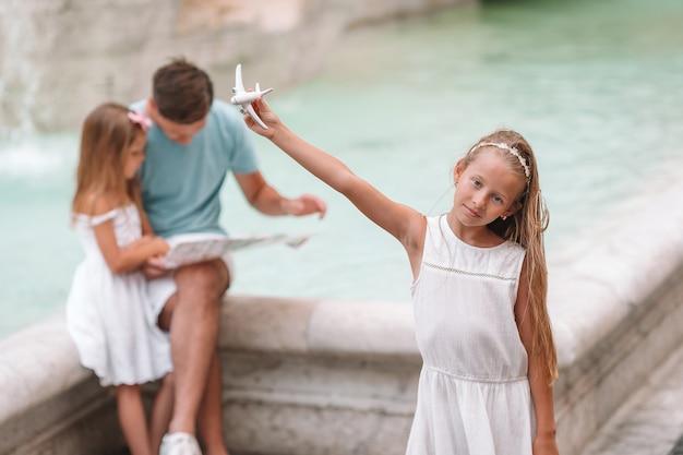 Familie mit touristischer karte nahe fontana di trevi, rom, italien. Premium Fotos
