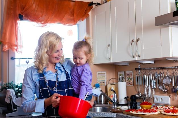 Familie - mutter und kind pizza backen Premium Fotos