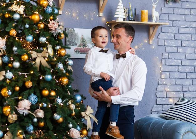 Familie neben einem weihnachtsbaum zu hause Premium Fotos