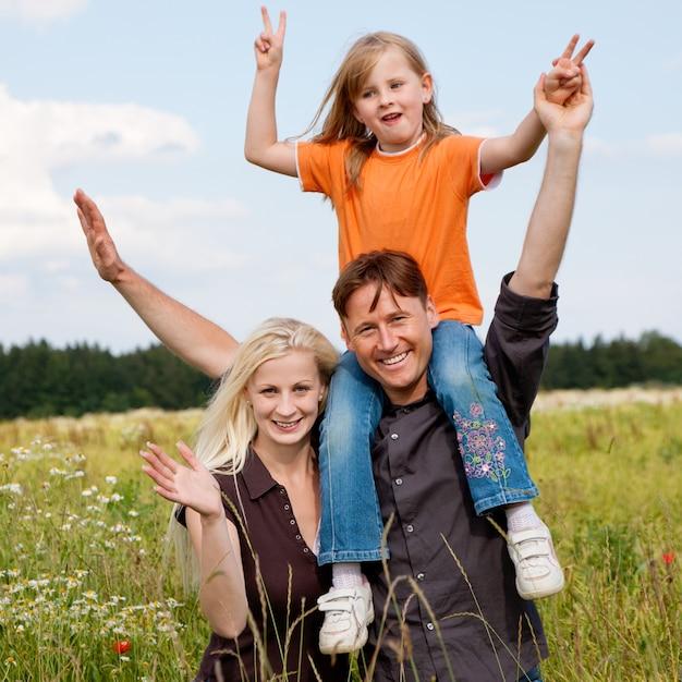 Familie posiert auf einer wiese Premium Fotos