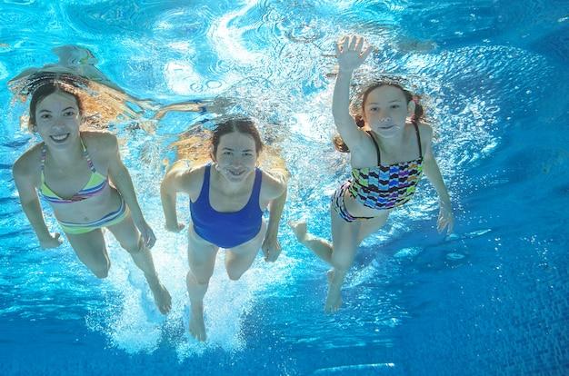 Familie schwimmt im pool unter wasser, glückliche aktive mutter und kinder haben spaß unter wasser, fitness und sport mit kindern in den sommerferien im resort Premium Fotos