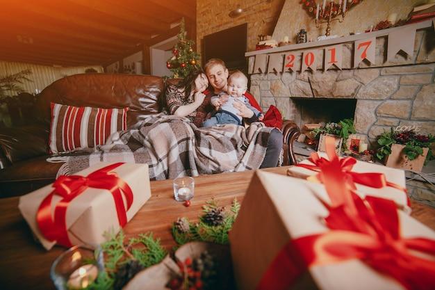 familie sitzt auf der couch in einer decke verkleidet und von den braunen tisch geschenke. Black Bedroom Furniture Sets. Home Design Ideas