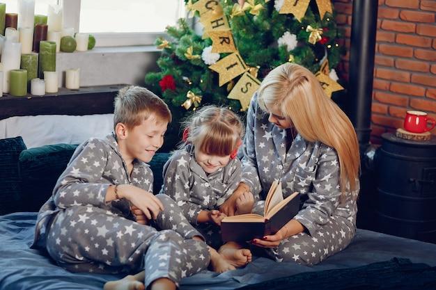 Familie sitzt auf einem bett Kostenlose Fotos