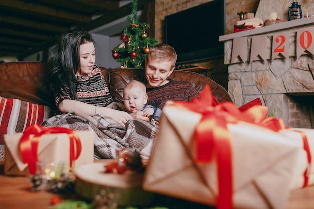 familie sitzt auf einer couch mit roten b ndern durch braun geschenke gesehen download der. Black Bedroom Furniture Sets. Home Design Ideas