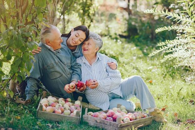 Familie sitzt in einem garten mit äpfeln Kostenlose Fotos